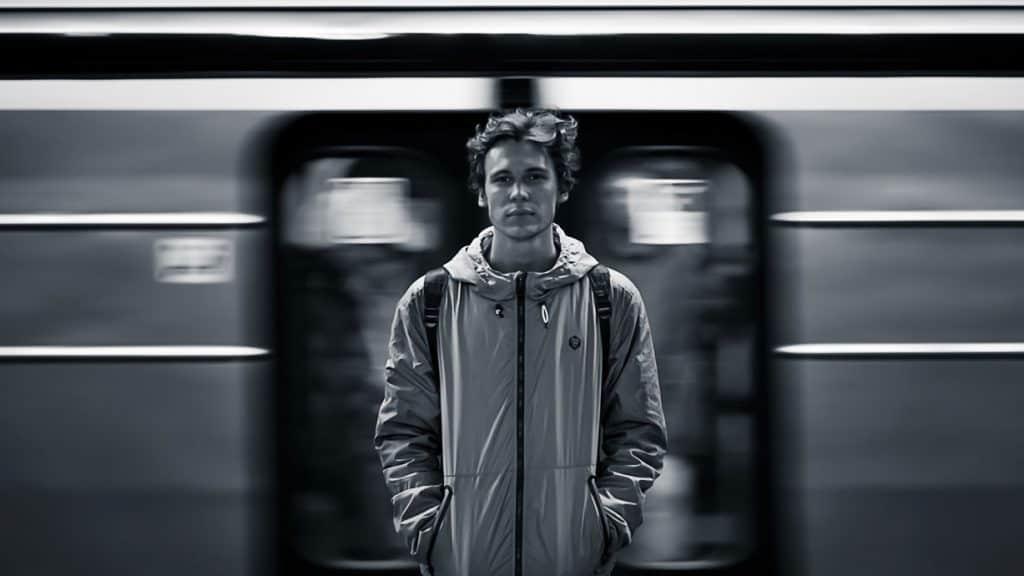 Junger Mann vor einfahrender Bahn