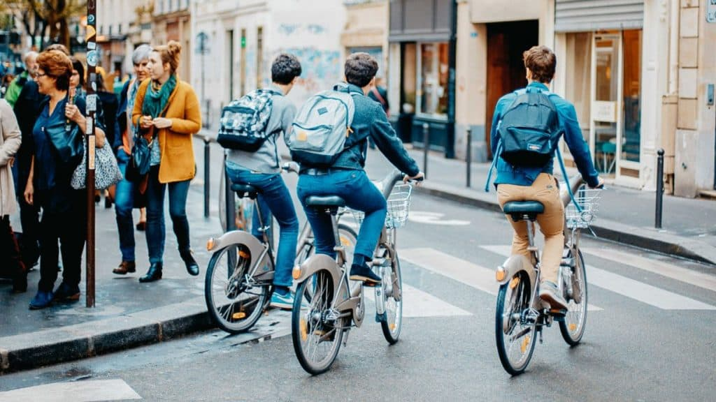 Drei Jugendliche fahren mit ihrem Fahrrad um eine Ecke