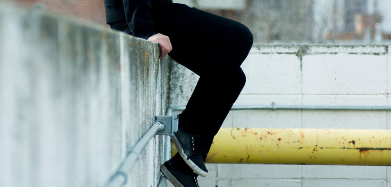 Beine eines jungen Mannes an einer Mauer