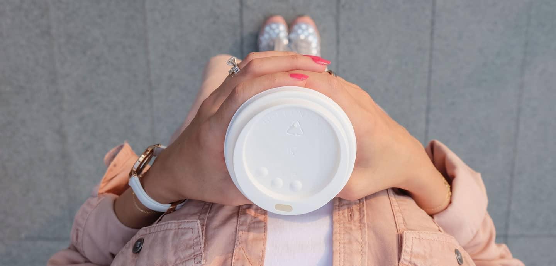 junge Frau mit umweltschädlichem Coffee-To-Go-Becher in der Hand