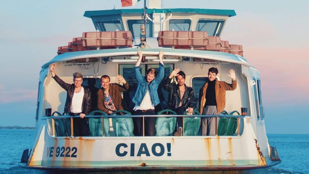 Die Band Wanda winkt von einem Boot