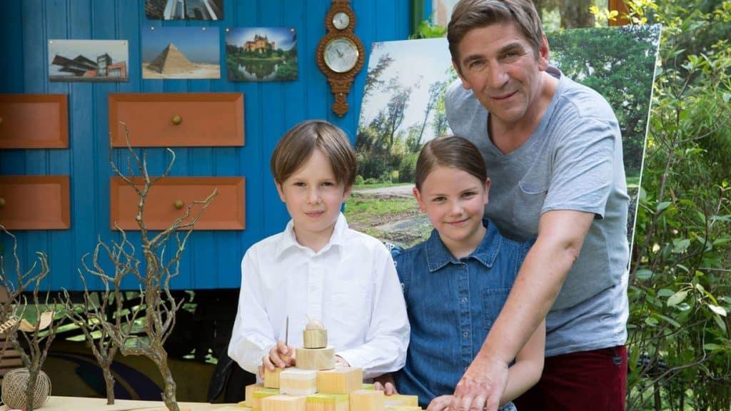 Guido Hammesfahr, Ellis und Benedikt schauen stolz auf das Modell einer Schule, was sie für Löwenzahn gebastelt haben