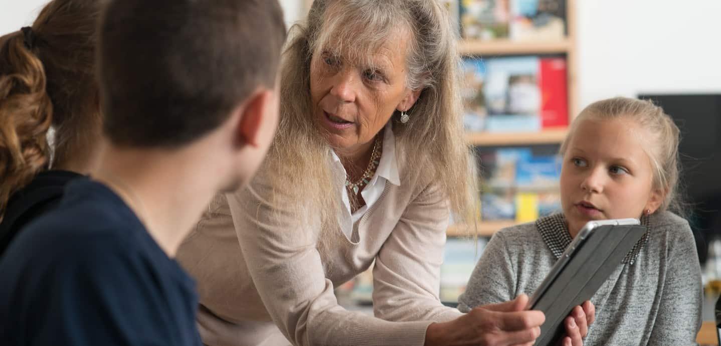 Eine Lehrerin erklärt ihren Schülerinnen wie sie Werbung erkennen können