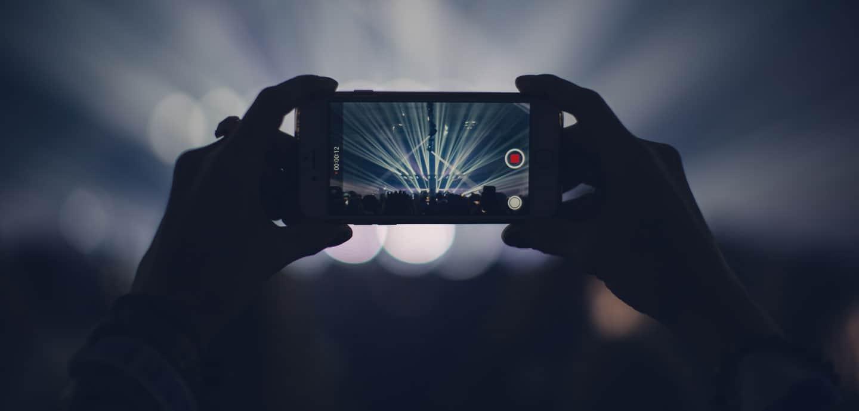 Jemand filmt ein Konzert mit seinem Smartphone