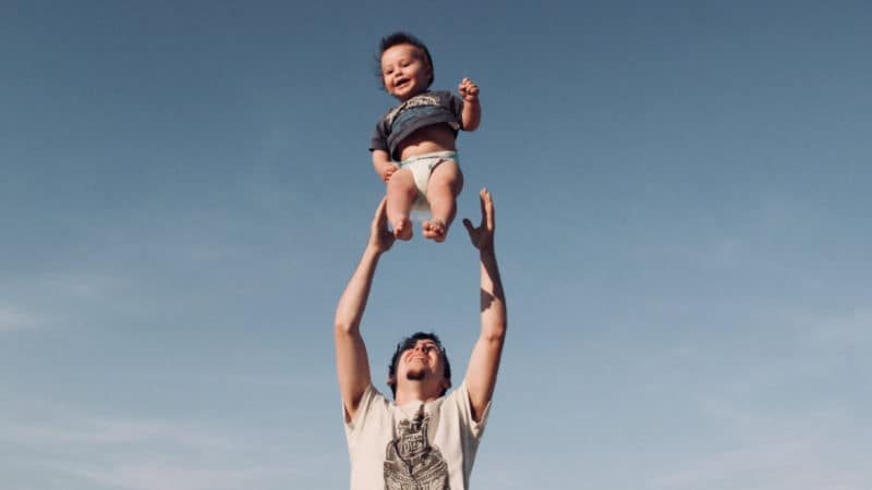 Ein Mann hält ein Kleinkind in den Himmel