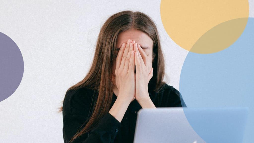 Frau vor Laptop vergräbt Gesicht in den Händen