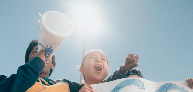 Kinder mit Megafon und Plakat