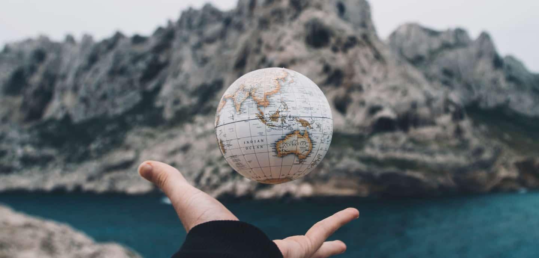 Hand wirft Globus in die Luft