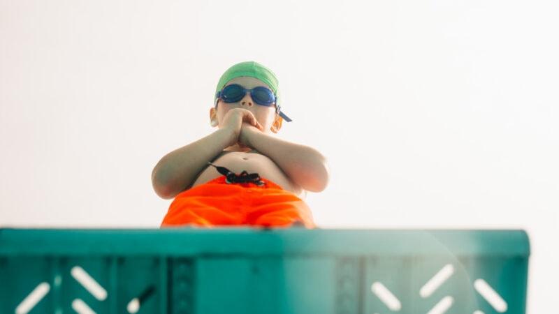 Kleiner Junge schaut vom Sprungbrett nach unten