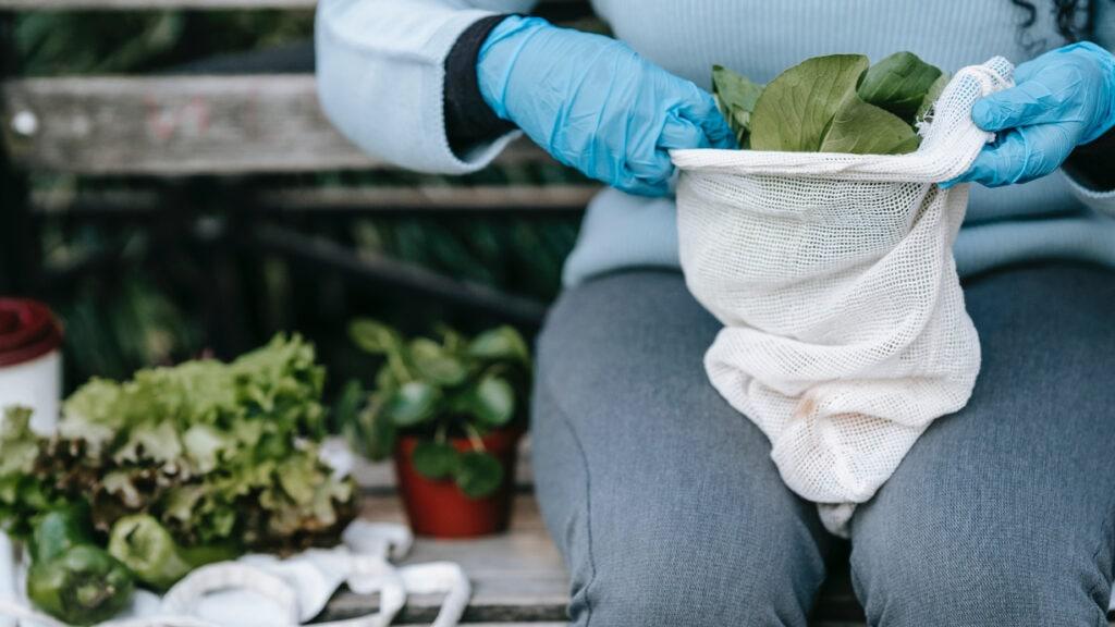 Junge Frau packt Salat in Baumwolltüte auf Bank