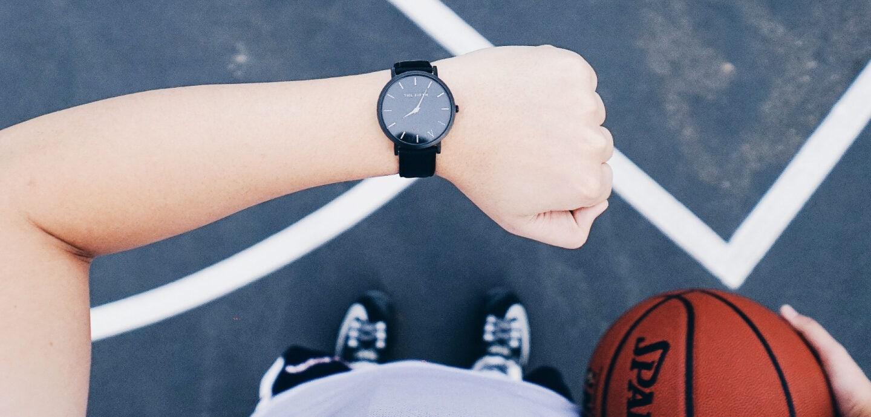 Basketballer schaut auf seine Uhr am Handgelenk