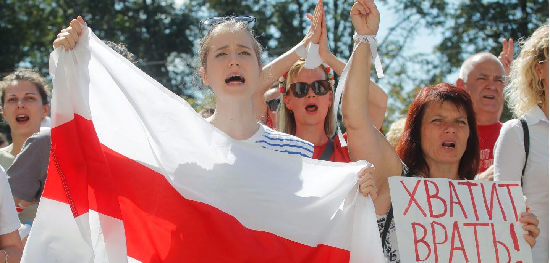 Proteste in Belarus, junge Frau hält Fahne hoch