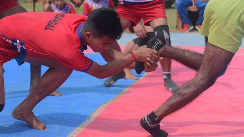 Spieler beim Kabaddi-Spiel umfgasst den Fuß eines Gegenspielers