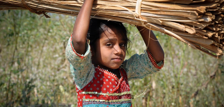 Kleines Mädchen trägt ein Bündel auf der Schulter