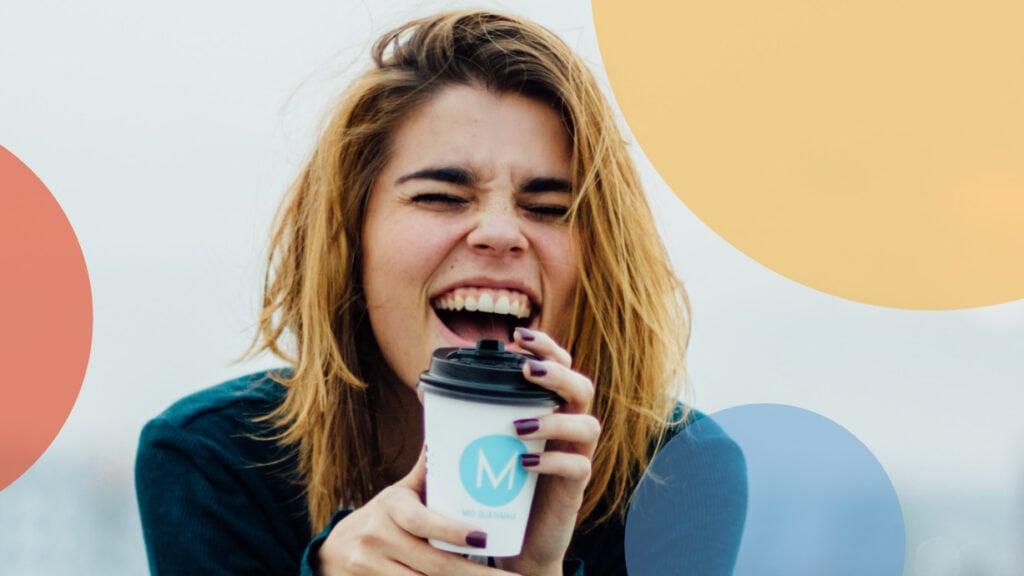 Frau lacht herzhaft mit Kaffeebecher in der Hand