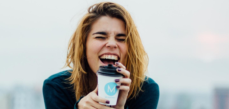 Frau lacht herzhaft mirt Kaffeebecher in der Hand