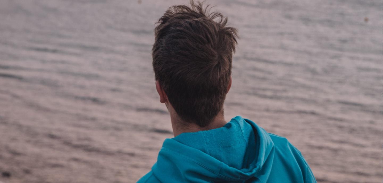 Junger Mann schaut aufs Wasser