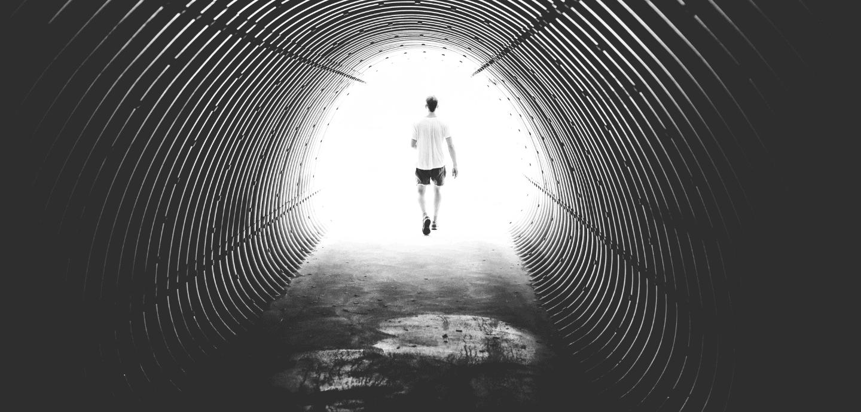Ein Mann geht durch einen dunklen Tunnel auf den hellen Ausgang zu.