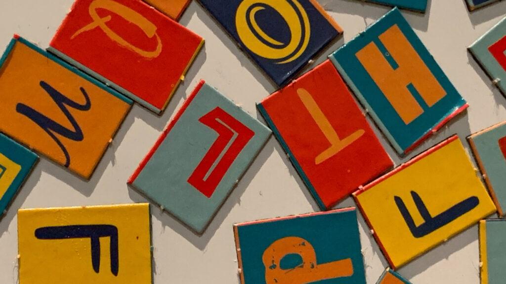 Bunte Buchstaben liegen verteilt über einen Tisch