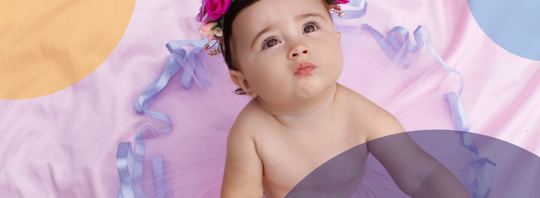 Ein Baby sitzt auf einer rosa Decke, trägt ein lila Tütü und rosafarbene Blumen im Haar.