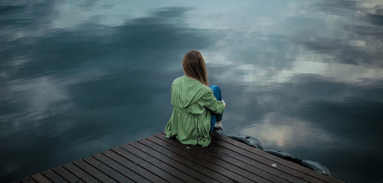 Eine Frau sitzt alleine auf einem Steg und guckt auf das Wasser.