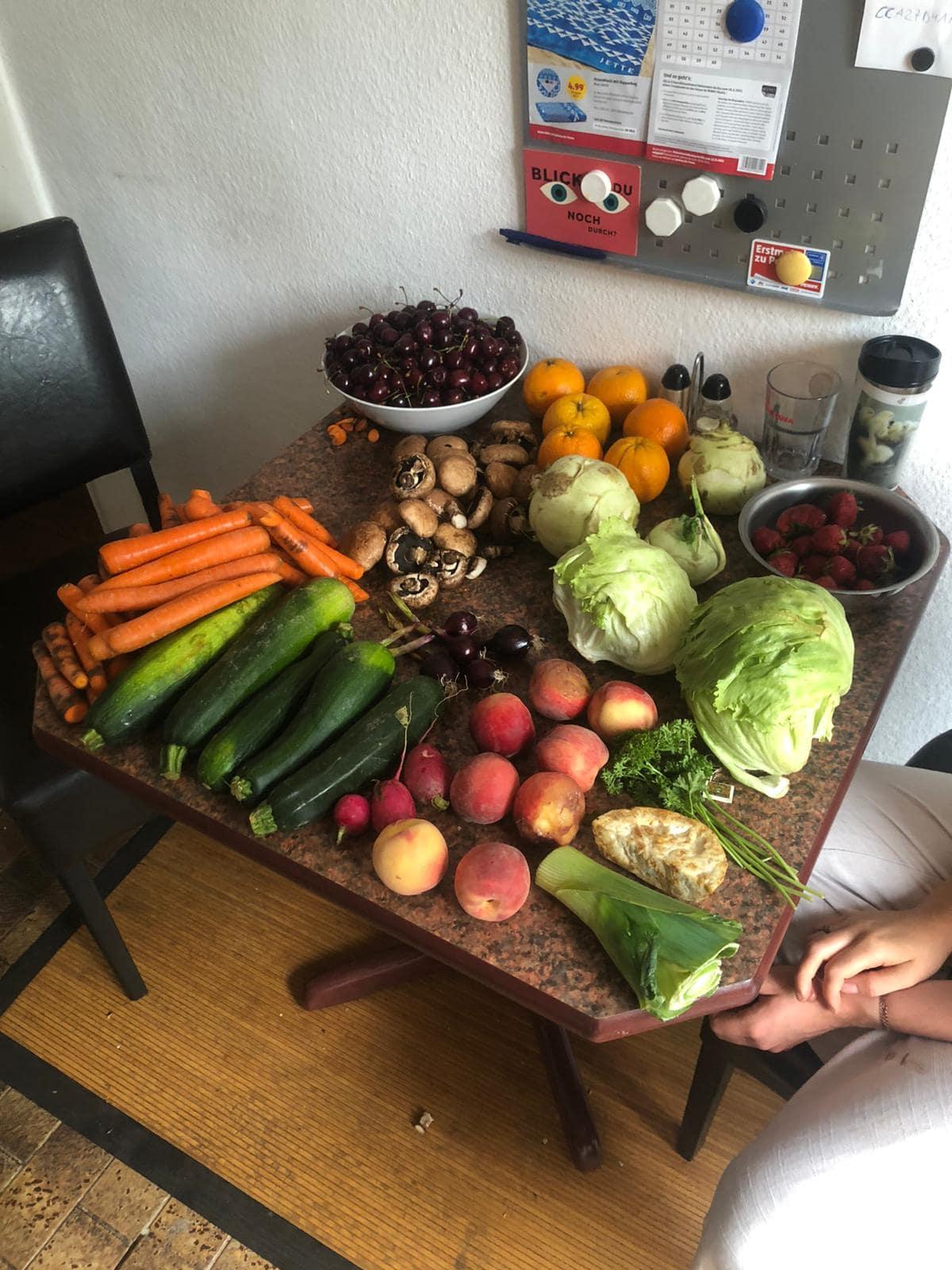 Obst und Gemüse liegen auf einem Esstisch.