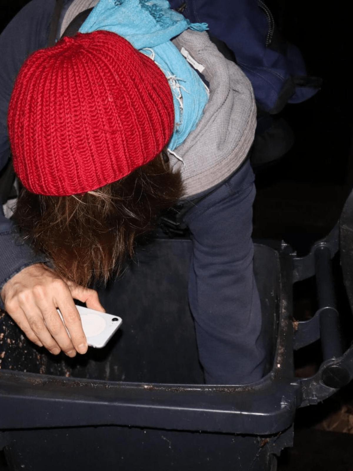 Marcoo Valentínoo schaut mit einer Handytaschenlampe in eine Mülltonne.