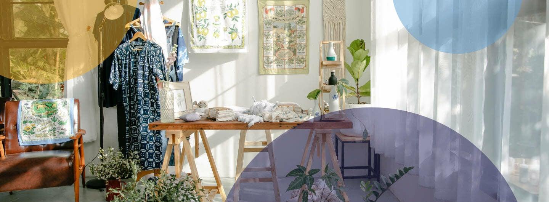 Ein Zimmer mit Klamotten, Bildern, einem Tisch und Pflanzen.
