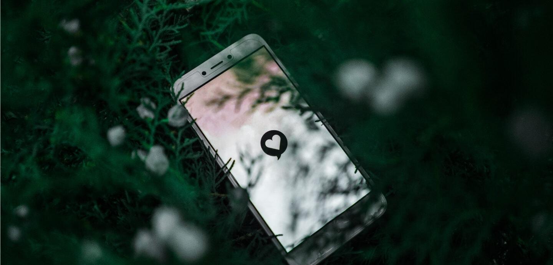 Ein Handy auf dessen Bildschirm ein Herz zu sehen ist, liegt auf dem Boden.