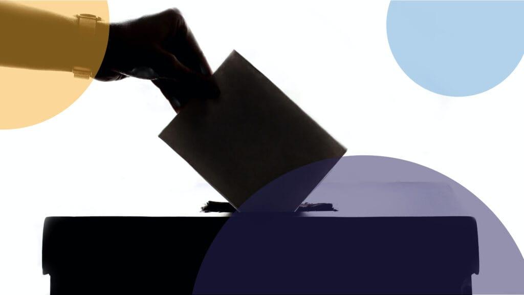 Eine Hand wirft einen Stimmzettel in eine Wahlbox