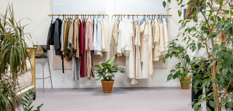 Eine Kleiderstange mit Klamotten und grüne Pflanzen.