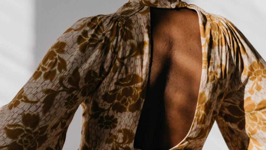 Der Rücken einer Frau in einem rückenfreien Kleid.
