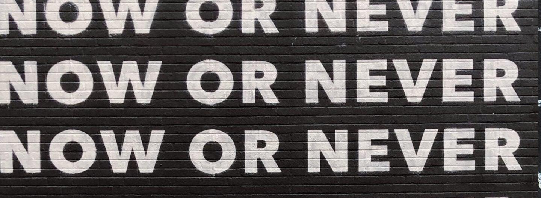 """Schrftzug """"Now or never"""" vier Mal übereinander auf einer Wand"""