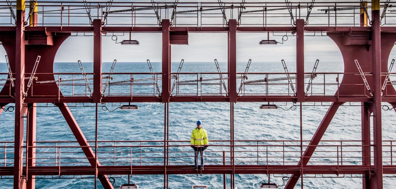 Julian Weiand steht mit einer gelben Jacke bekleidet auf dem Schiff, hinter ihm ist das Meer