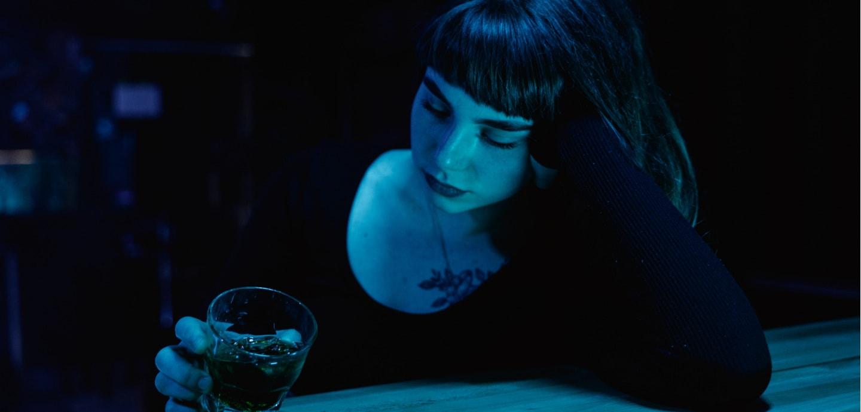 Frau sitzt missmutig an der Bar vor einem Glas gefüllt mit Alkohol