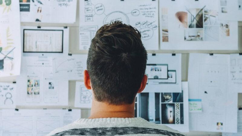 Mann steht vor einer Wand voller Zettel