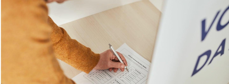 Ein älterer Mann füllt einen Wahlzettel aus.