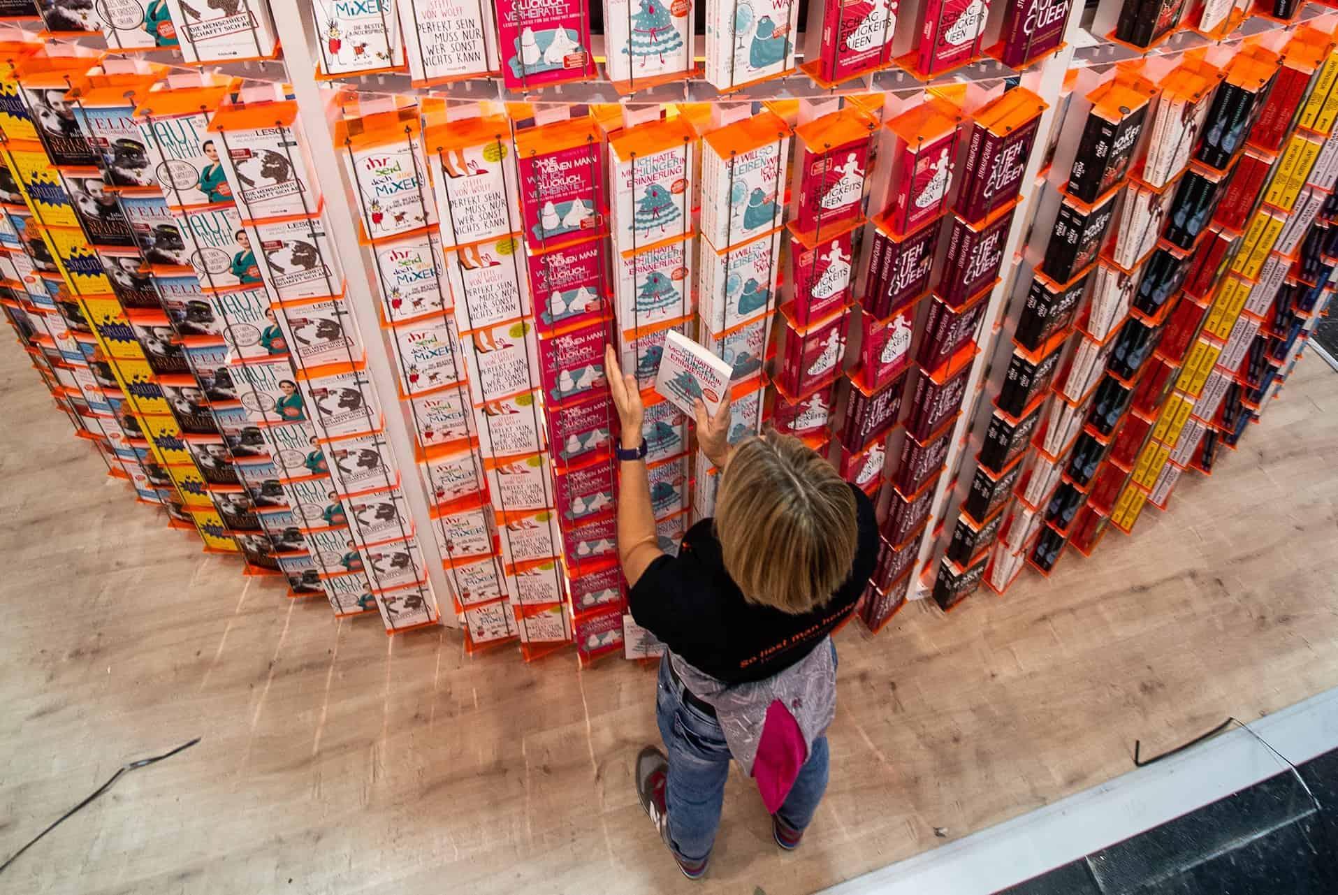 Eine Frau steht vor einem riesigen Bücherregal