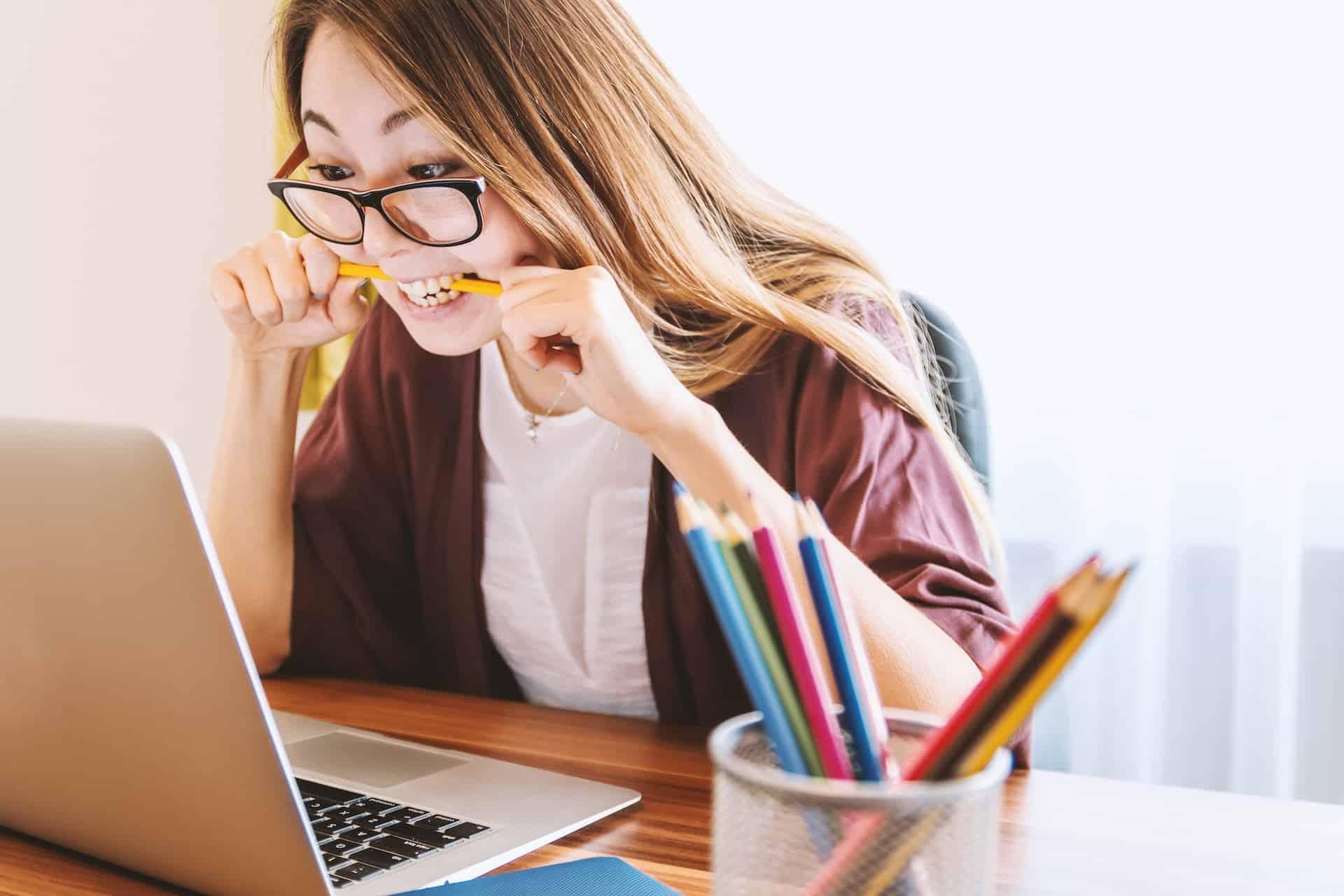 Frau sitzt am Schreibtisch und beisst auf einen Buntstift