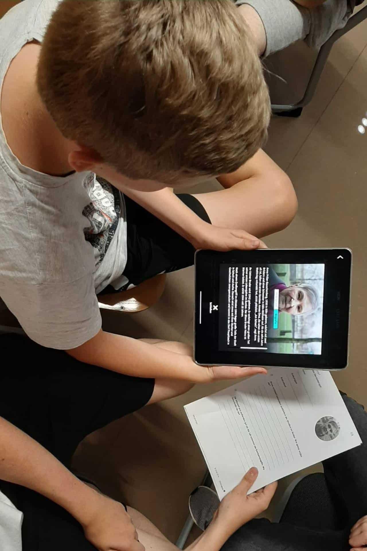Ein Junge schaut interessiert auf ein iPad