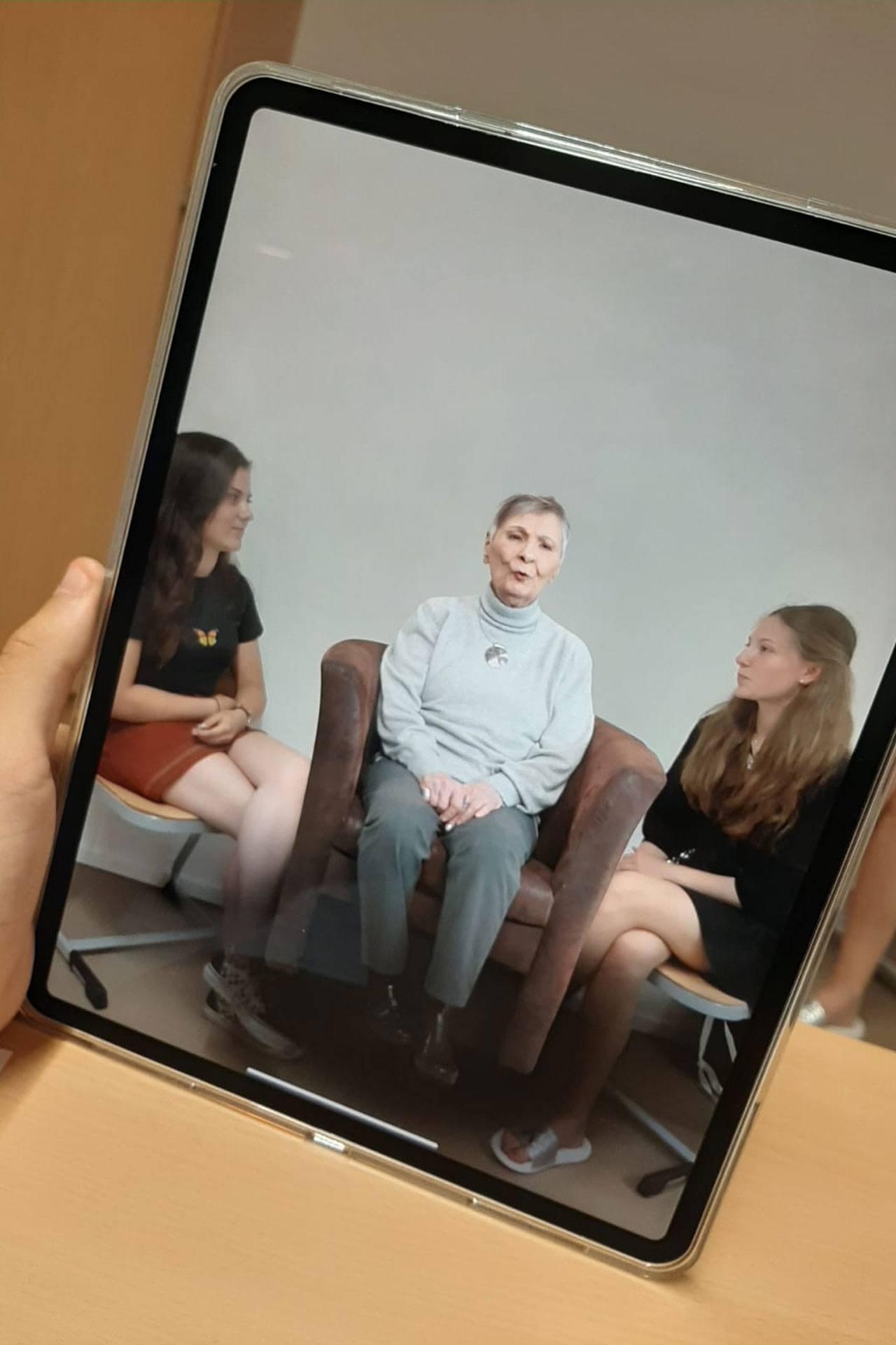 iPad, auf dem drei Frauen zu sehen sind, die sich unterhalten