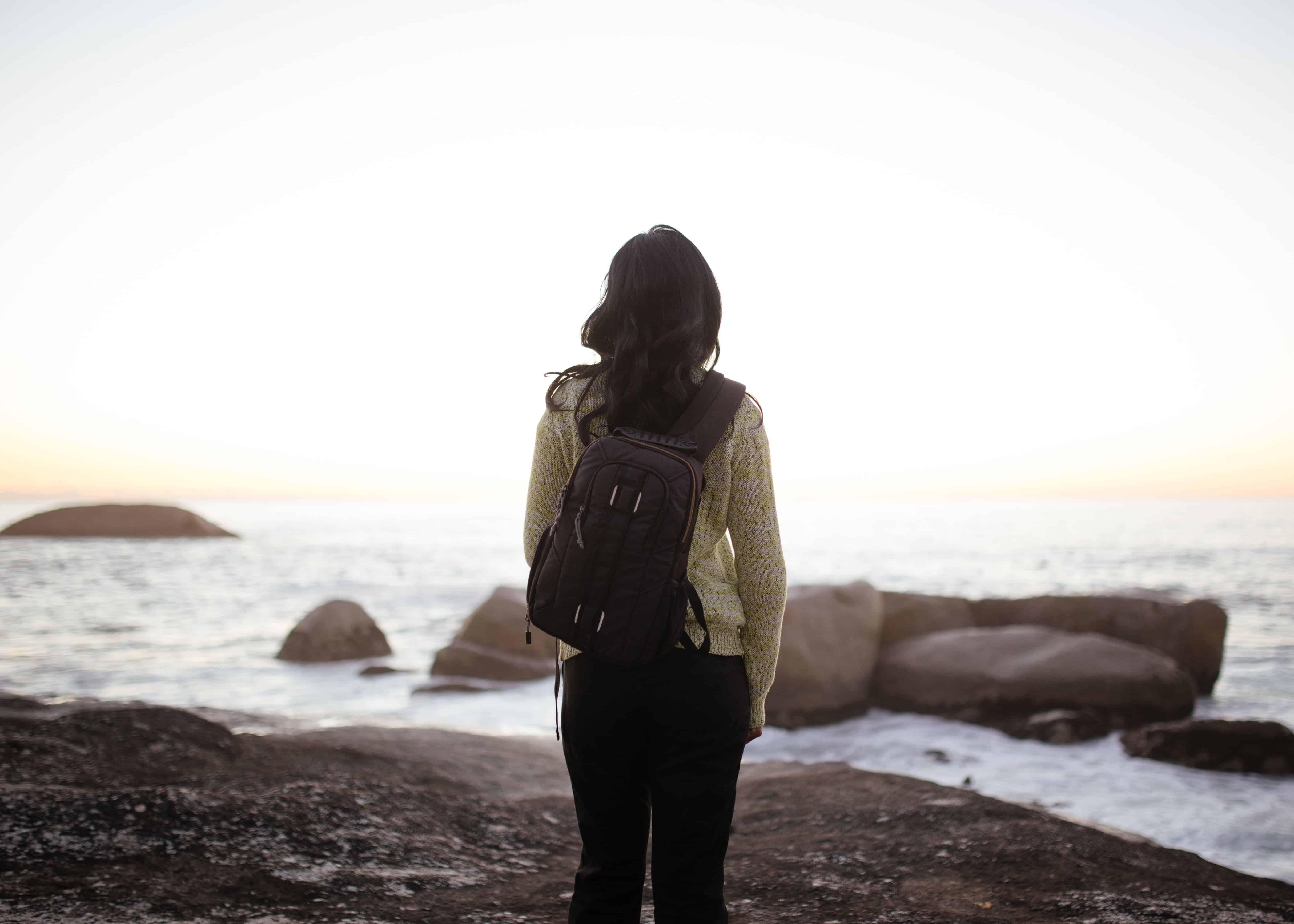 schwarzhaarige Frau mit Rucksack steht am Meer