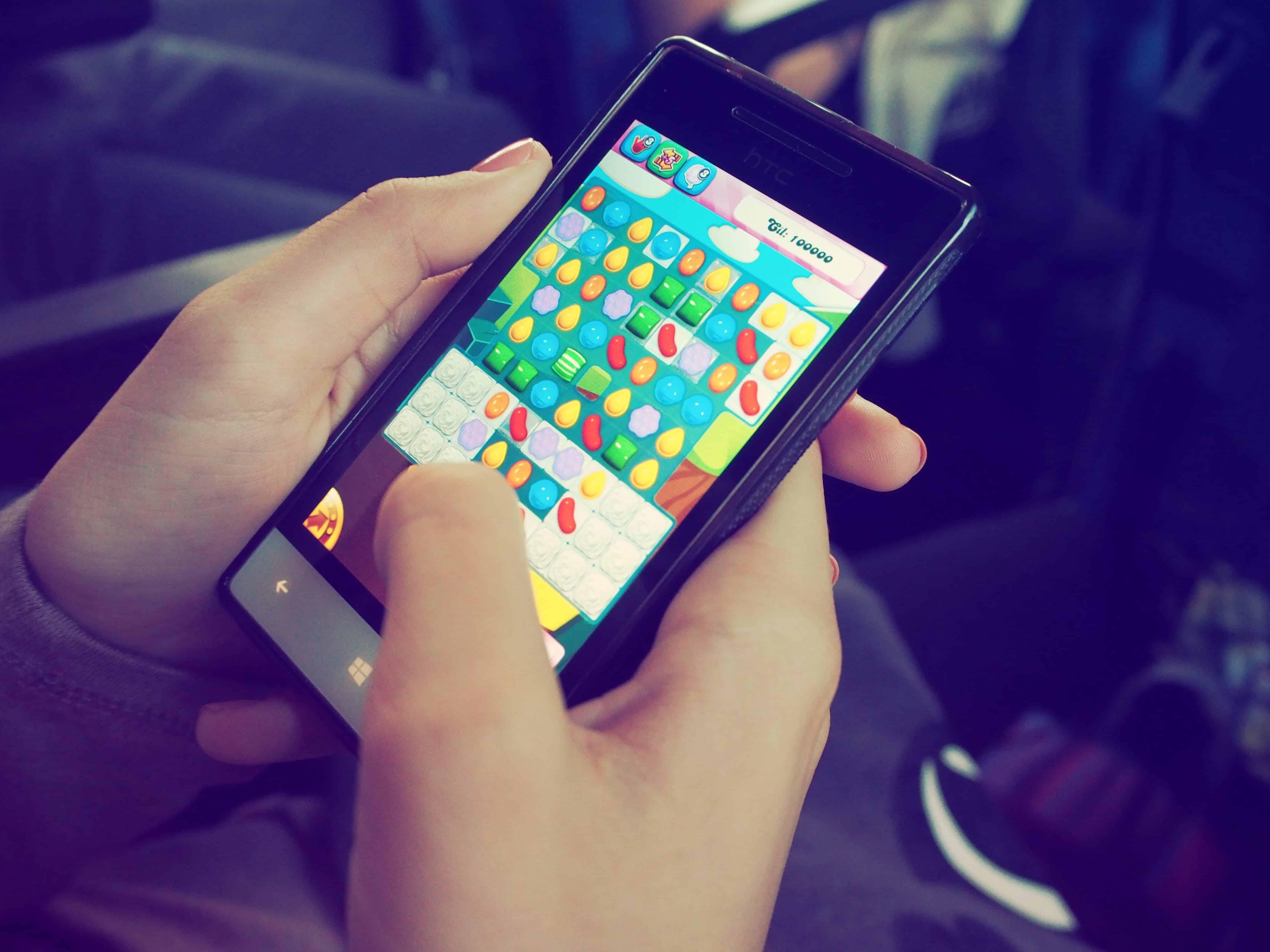Person spielt Candy Crush auf dem Handy