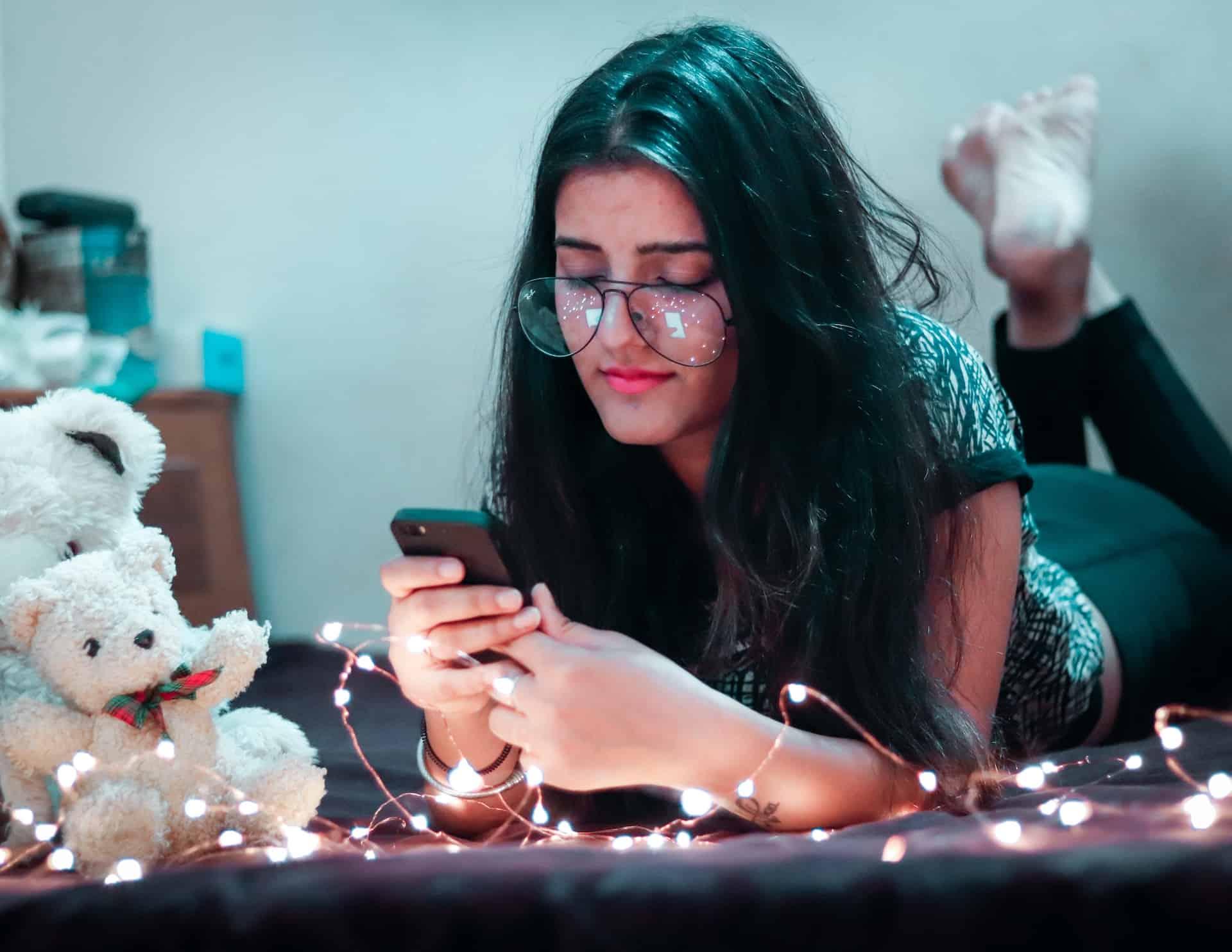 Frau liegt auf dem Bauch und schaut auf ihr Handy