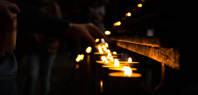Teelichter werden in einer dunklen Kirche angezuendet