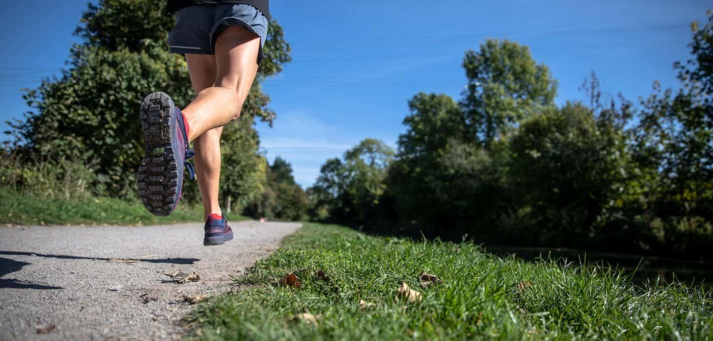 eine Person joggt auf einem Weg im Gruenen.